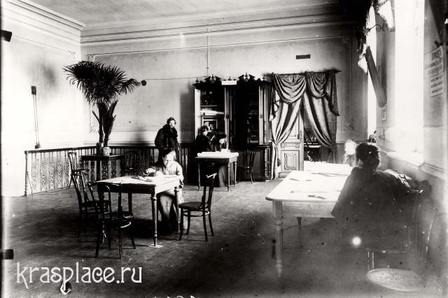 Фойе народного дома. За столом сидит М.В.Красноженова